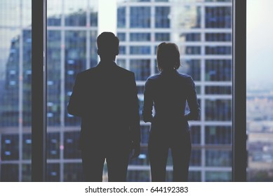 Rear view silhouettes of two business partners looking thoughtfully out of a office window in situation of bankruptcy,team of businesspeople in fear or risk watching cityscape from skyscraper interior