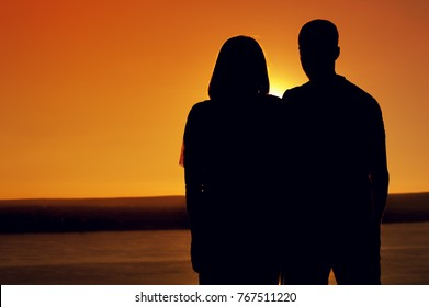 Rear view - silhouettes of yong man and woman standing together and admiring the sea during sunset in summer