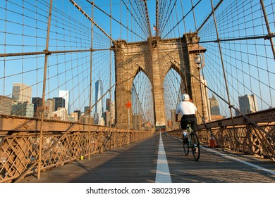 Rear View of Single Cyclist Riding on Pedestrian Pathway Through Iconic Arches of Historic Brooklyn Bridge at Sunset, Looking Towards Manhattan, New York City, New York, USA