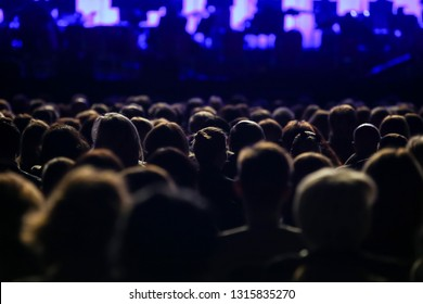 Rear view of sitting audience on a concert, silhouette, close up.