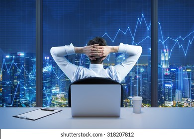 Rear view of sitting businessman who is looking at the city from the modern panoramic office. New York evening view. Crossed hands on the head. Financial charts are drawn over the panoramic windows.