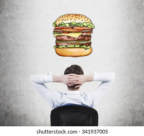A rear view of sitting relaxing man who is dreaming about burger. A fast food concept. Concrete background.