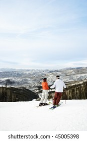 Rear view of skiers on ski slope with mountains in background. Vertical shot.