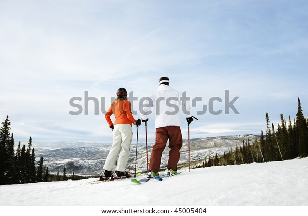 Rear view of skiers on ski slope with mountains in background. Horizontal shot.