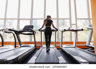 Rear view slim young woman fitness model runs on a treadmill and looks out the window with a beautiful landscape. Concept of cardio for fat loss