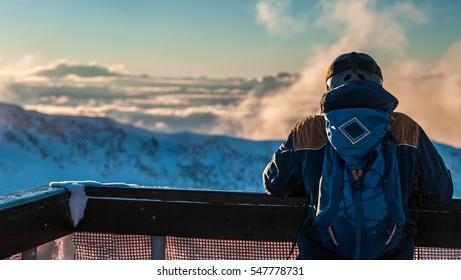 Rear view of snowboarder watching mountains landscape