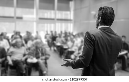 Rear view of speaker giving a talk at business meeting. Audience in the conference hall. Business and Entrepreneurship concept. Black and white image.