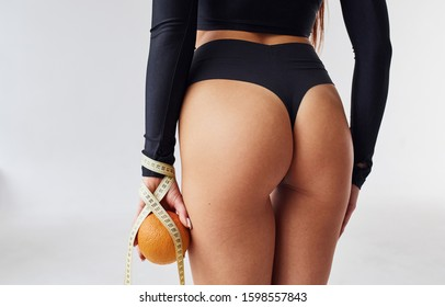 Rear view of sportive woman with orange and measuring tape in the studio.