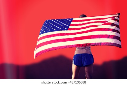 Rear view of sportsman is raising an american flag against blurred mountains