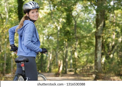 rear view of sporty female rider cycling