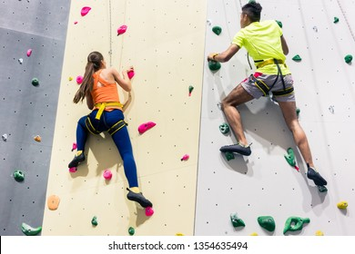 Rear view of a sporty people climbing wall