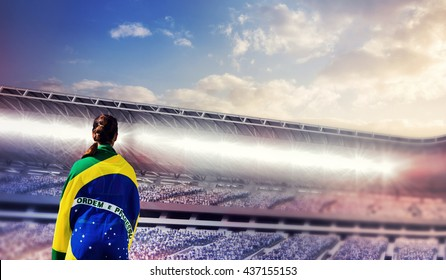 Rear view of sporty woman holding the Brazilian flag against composite image of arena sport against cloudy sky