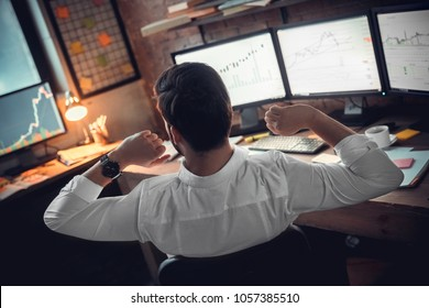Rear view at stock trader broker stretching hands at workplace