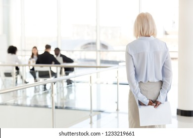 Rear view at stressed nervous middle aged senior old business woman applicant waits for job interview holding papers behind back preparing for performance feel afraid of public speaking fear concept