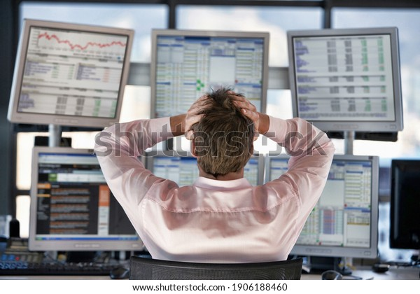 Rear view of stressed stock trader looking on computer screens