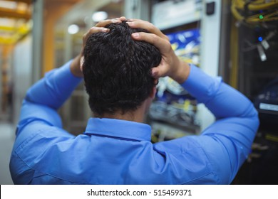 Rear view of stressed technician working on server maintenance