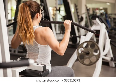 Rear view of a strong and athletic woman working out on a lat pulldown machine
