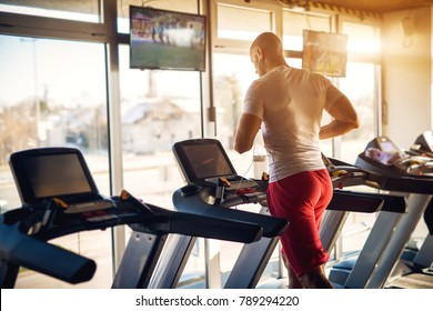 Rear view of strong motivated and focused muscular bald bodybuilder man running on the treadmill with earphones in the modern sunny gym with tv in front.