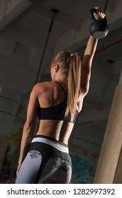 Rear view - strong woman lifting kettle bell overhead. Sportive female during workout in the gym. Cross strength training