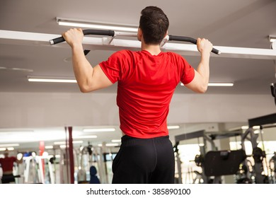 Rear view of a strong young man doing pullups at the gym