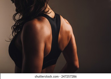 Rear view of strong young woman wearing sports bra. Muscular back of a woman in sportswear.