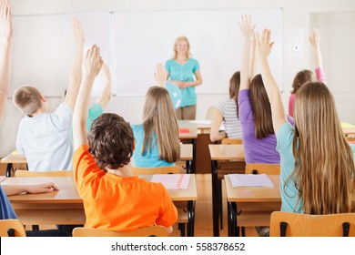 Rear view of students in bright classroom responding to the teacher's question, raising their arms up