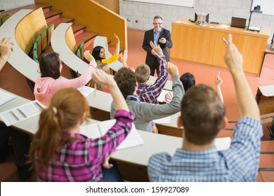 Rear view of students raising hands with a teacher in the college lecture hall