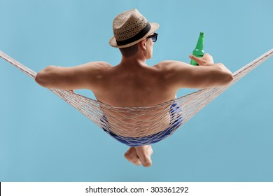 Rear view studio shot of a carefree young man lying in a hammock and holding a bottle of beer on blue background