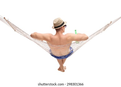 Rear view studio shot of a relaxed young man lying in a hammock and holding a bottle of beer isolated on white background