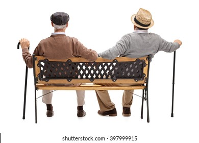 Rear view studio shot of two relaxed senior gentlemen sitting on a wooden bench isolated on white background