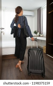 Rear view of stylish business lady in blouse coming in small hotel room with bed and wardrobe and carrying luggage, she checking in hotel