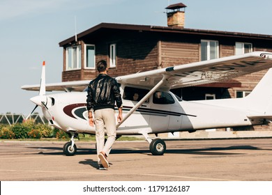 rear view of stylish male pilot in leather jacket walking near airplane