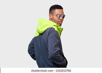 Rear view of stylish mixed race man looks with concentrated expression, wearing green hoody, looking through mirror glasses. African American male posing on white studio wall. People and emotions