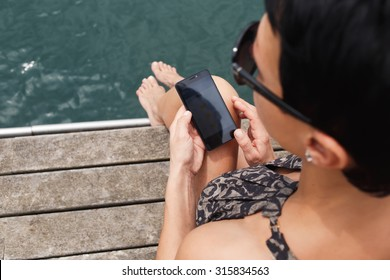 Rear view of stylish woman holding cell telephone with copy space area for your text message or advertising content, female chatting on her mobile phone while relaxing on a wooden pier against water