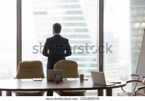 Rear view at successful contemplative businessman standing back in modern office looking at window thinking of future business challenges, dreaming hoping considering new opportunities vision concept