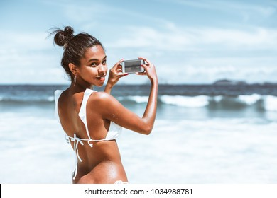 Rear view of svelte young Brazilian girl in swimsuit with wet skin, half-turned and looking at camera while taking photos of beautiful seascape and islands in front of her after swimming in ocean