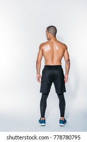 rear view of sweaty african american sportsman standing on white