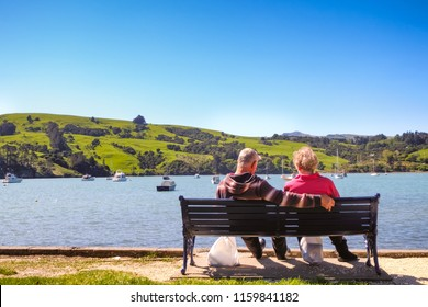 Rear view of a sweet aging couple sitting together on bench outdoors. They enjoy the beautiful nature New Zealand landscape.