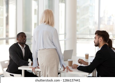 Rear view of team leader, company owner talking with serious multiracial business people sitting in modern office at boardroom during meeting. Employees listening mature experienced mentor at briefing