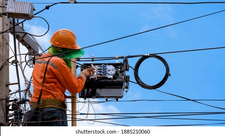 Rear view of technician on wooden ladder checking fiber optic cables in internet splitter box on electric pole against blue sky background - Shutterstock ID 1885210060