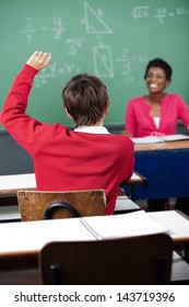 Rear view of teenage schoolboy raising hand at desk with teacher in background