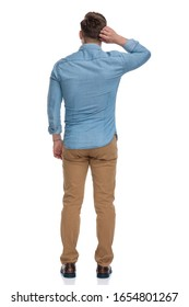 Rear view of a thinking casual man scratching his head, standing on white studio background
