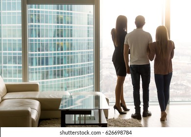 Rear view of three business people standing by the full length floor-to-ceiling window in office, looking at big city scenery. Real estate agent showing apartment to couple, enjoying birds-eye view