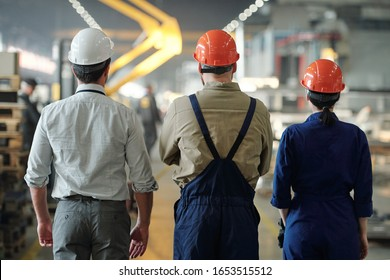 Rear view of three contemporary professionals in helmets and workwear standing in aisle inside workshop of industrial plant