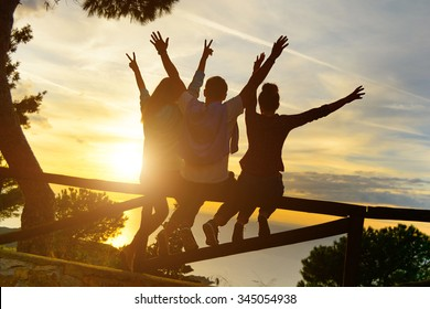 Rear view of three couple best friends travelers put hands up at sunset. Young  relaxing hipster wanderers enjoying exclusive alternative destination. Holiday life moment at warm orange light