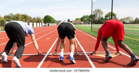 Rear view of three high school track sprinters in the set position at the starting line ready to run down the track in lanes.