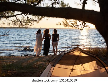Rear view of three slim tourist girls standing on lake shore in front of small tent enjoying beautiful panorama of sunset and crystal blue clear lake water. Tourism, friendship and camping concept.