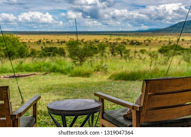 Rear view of timber outdoor chairs on the verandah of an exclusive, luxury safari tent overlooking the Serengeti grasslands. Selective focus. African landscape. Kiota Camp, Seronera Valley, Tanzania.