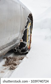 Rear view of tire chains on car wheel on dirty vehicle in snow