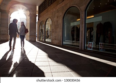 Rear view of a tourist couple silhouette holding hands and turning while on vacation, walking under an old arch with the morning sun rays filtering through.